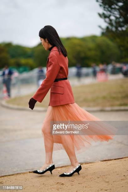Guest wears earrings, a light rust-color jacket, a black belt, a glittering peach-color tulle flowing front-slit tutu skirt, black and white Dior...
