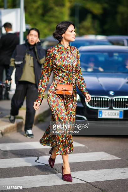 Guest wears earrings, a lustrous colorful print long sleeves dress, a tan-color bag, purple pointy heeled shoes, outside the Tod's show during Milan...
