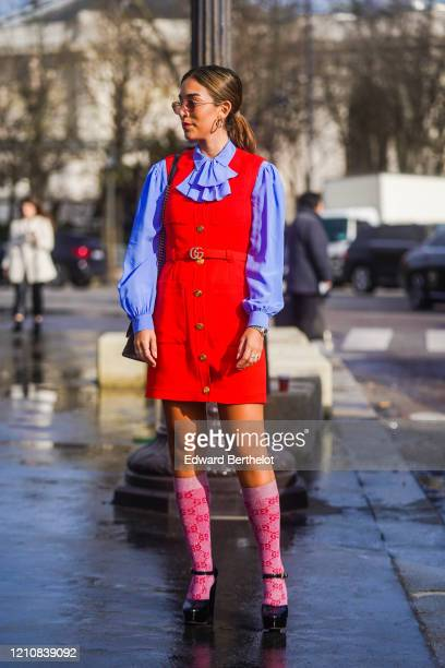 Guest wears earrings, a mauve ruffled shirt, a red sleeveless dress, a Gucci belt, Gucci monogram long socks, black shoes, outside Chanel, during...