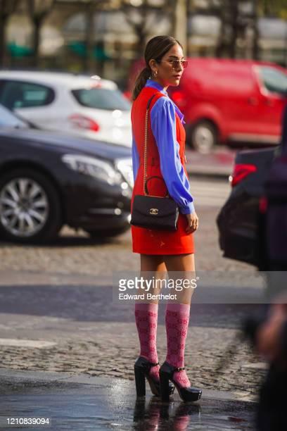 Guest wears earrings, a mauve ruffled shirt, a red sleeveless dress, a Gucci belt, Gucci monogram long socks, black shoes, a Chanel bag, outside...