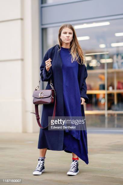A guest wears earrings a navy blue coat a blue maxi dress a shiny Chloe burgundy bag navy blue sneakers during London Fashion Week February 2019 on...