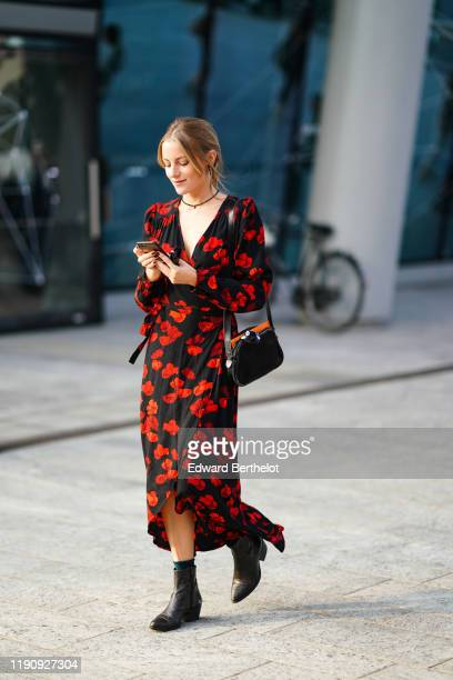 Guest wears earrings, a necklace, a black bag, a black long sleeves v-neck hi-low ruffled dress with red floral print, dark brown crocodile pattern...