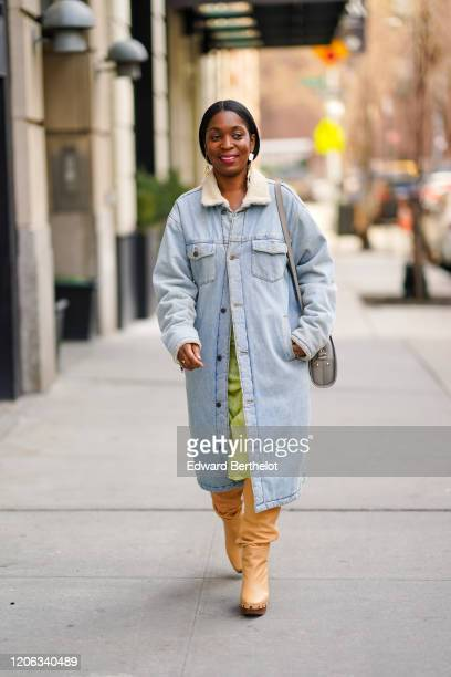 A guest wears earrings a pale blue denim long coat a green skirt pale orange boots a gray bag during New York Fashion Week Fall Winter 2020 on...