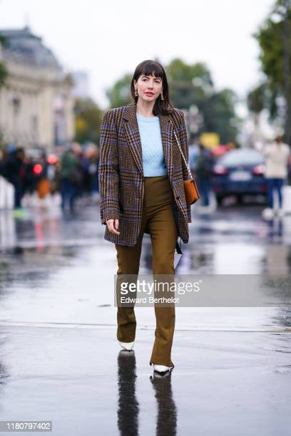 A guest wears earrings a printed pattern brown and blue jacket a pale blue top khaki flare pants white shoes a brown bag outside Chanel during Paris...