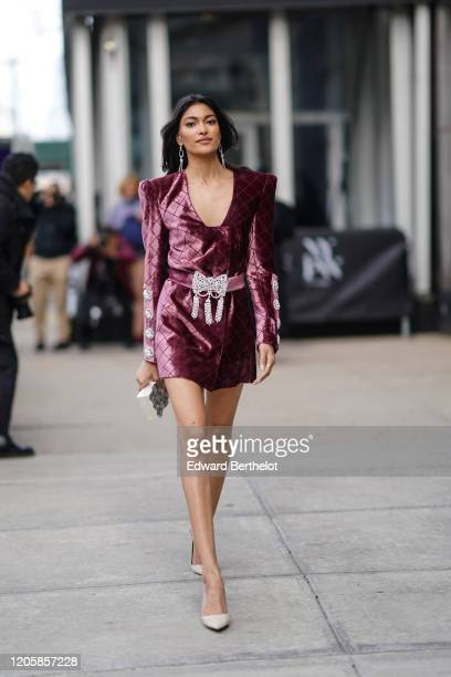 Guest wears earrings, a purple shiny dress, a bejeweled belt, pointy shoes, during New York Fashion Week Fall Winter 2020, on February 12, 2020 in...