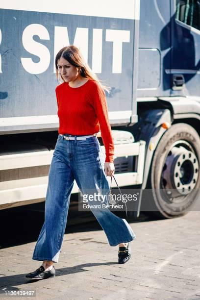 Guest wears earrings, a red sweater, a white belt, blue wide leg denim pants, black moccasins, a black bag, during London Fashion Week February 2019...