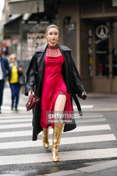 Guest wears earrings, a red thigh-slit dress with a red lace yoke, a black leather coat, a burgundy snake skin pattern handbag, shiny golden-tone...