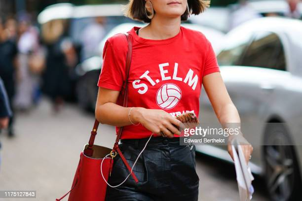 "Guest wears earrings, a red t-shirt with a logo print ""ST.ELM"", a red bucket bag, a black leather skirt, during London Fashion Week September 2019 on..."