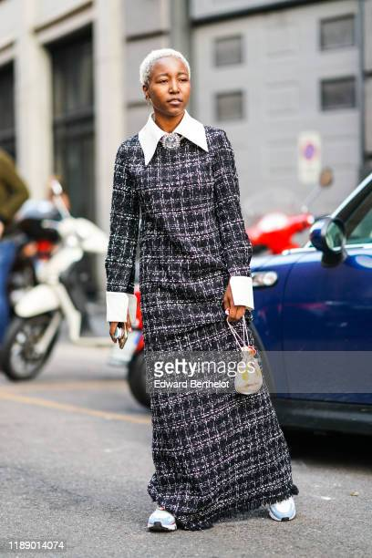 Guest wears earrings, a rhinestone brooch, a black and white tweed fringed long sleeves dress with white collar and cuffs, a beige purse with yellow...