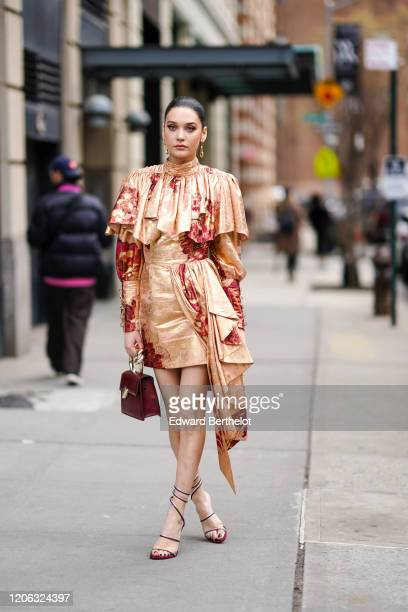 A guest wears earrings a ruffled shiny bronze color dress with red floral prit a burgundy leather bag high heel shoes during New York Fashion Week...