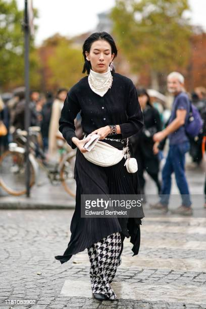 A guest wears earrings a scarf decorated with pearl embroideries a white Chanel bag with a white coin purse a black gathered top a black flowing...