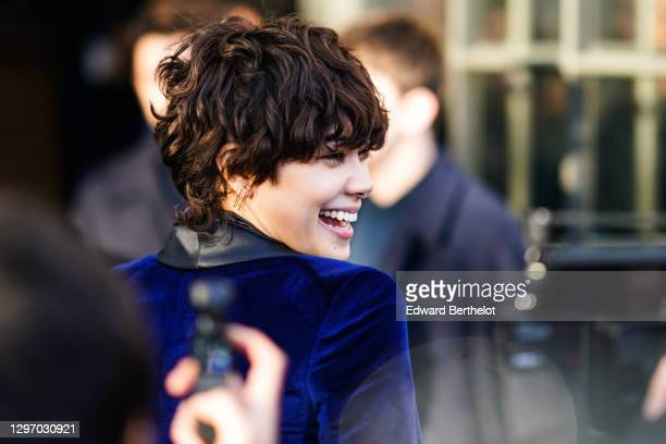 Guest wears earrings, a silky black scarf, a deep blue velvet jacket with lustrous black lapels, outside Paul Smith, during Paris Fashion Week -...