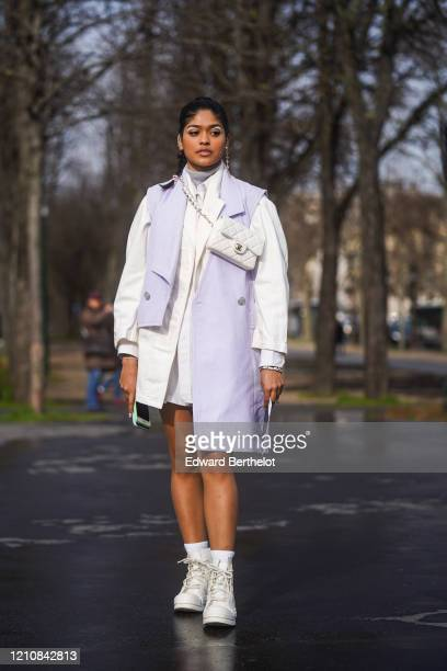 A guest wears earrings a turtleneck pullover a pale purple sleeveless jacket a white jacket white sneakers a crossbody white quilted Chanel bag...