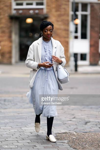 A guest wears earrings a white blazer jacket a blue lace dress a white bag during London Fashion Week Men's January 2019 on January 05 2019 in London...