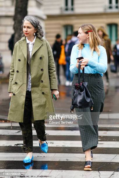 Guest wears earrings, a white frilly shirt, a light khaki trench coat, deep khaki camouflage pants, shiny blue pointy moccasins with sculpted heels ;...