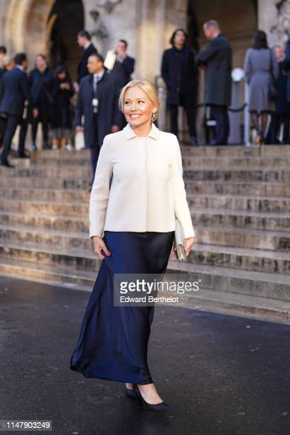 A guest wears earrings a white jacket a blue silky skirt shoes a clutch outside the Opera Garnier 350th Anniversary Gala in Paris on May 08 2019 in...