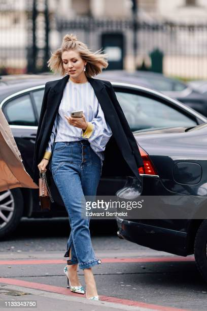 A guest wears earrings a white jacket a light blue striped and yellow lined top cuffed jeans a brown bag green and blue floral design white pointy...