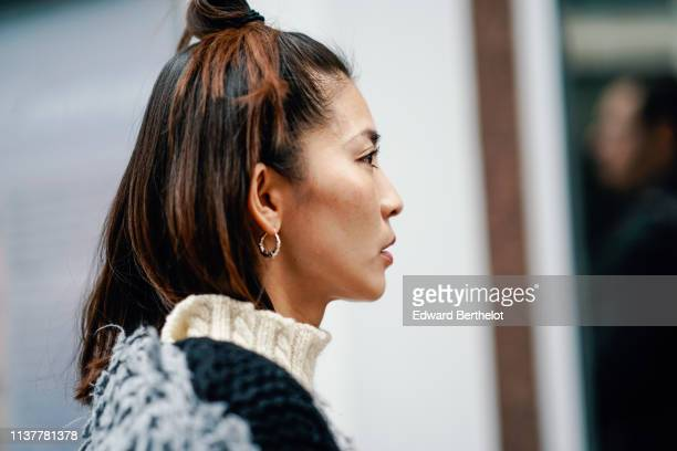 A guest wears earrings a white knit turtleneck a roughly knit sweater during London Fashion Week February 2019 on February 16 2019 in London England