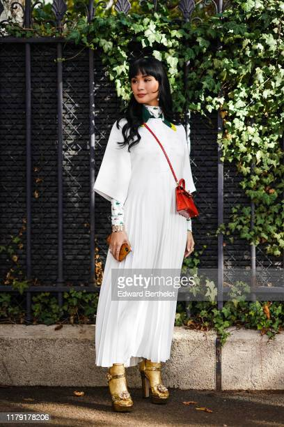 Guest wears earrings, a white pleated dress, a red bag, a turtleneck top with printed Lacoste logos depicting crocodiles, golden shoes, outside...