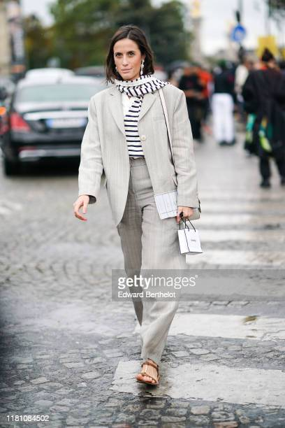 Guest wears earrings, a white scarf with navy blue stripes, a beige oversized jacket, light grey wide-legs full-length pants, brown leather flat...