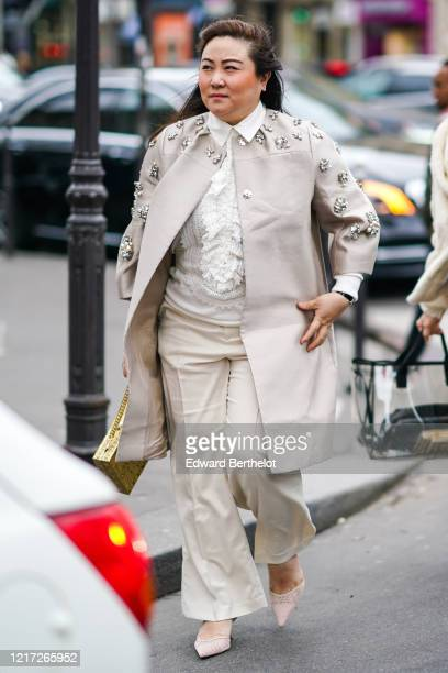 Guest wears earrings, a white shirt with a frilly white lace bib, a light grey coat with rhinestone and pearl embroideries, cream-color flare pants,...