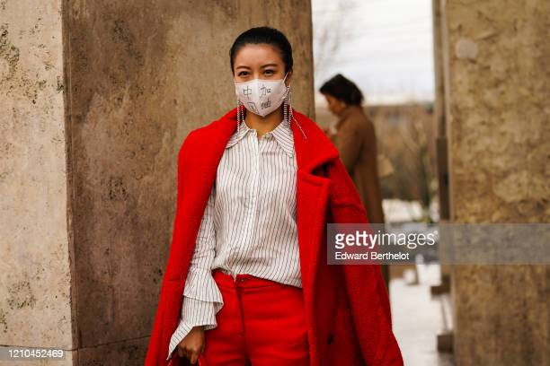 Guest wears earrings, a white shirt with thin black stripes, a red oversized coat, red pants, outside Akris, during Paris Fashion Week - Womenswear...