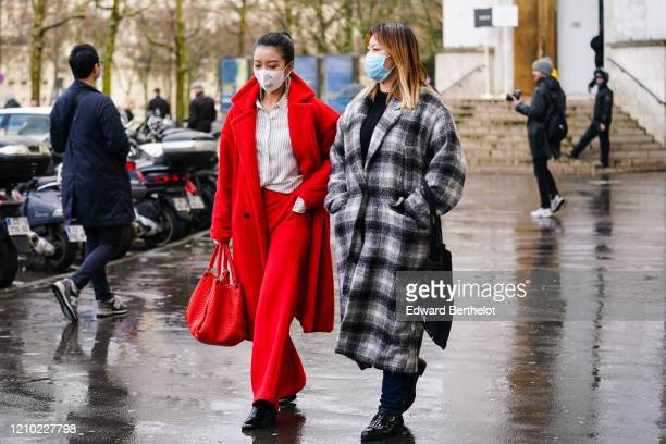 A guest wears earrings a white shirt with thin black stripes a red wool coat red pants black boots with steel tips a red woven leather bag a face...