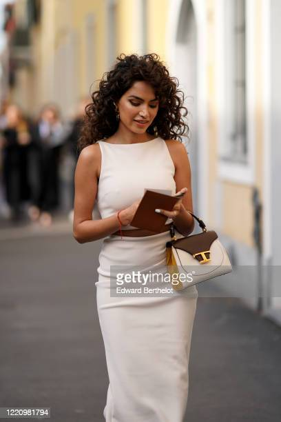 Guest wears earrings, a white sleeveless dress, a Tod's bag, outside Tod's, during Milan Fashion Week Fall/Winter 2020-2021 on February 21, 2020 in...