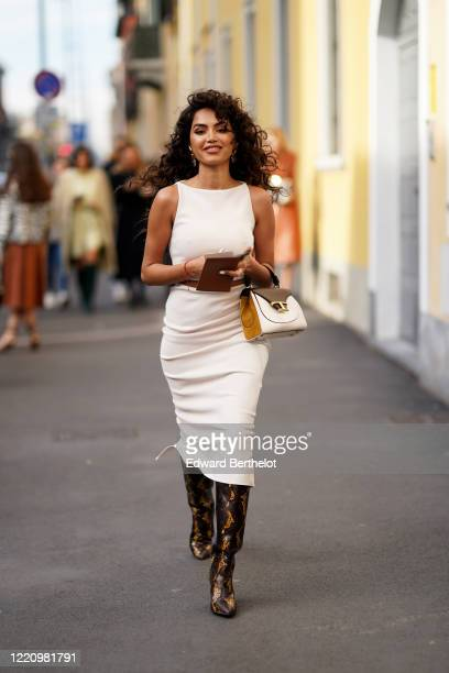 Guest wears earrings, a white sleeveless dress, a Tod's bag, snake print pointy leather boots, outside Tod's, during Milan Fashion Week Fall/Winter...