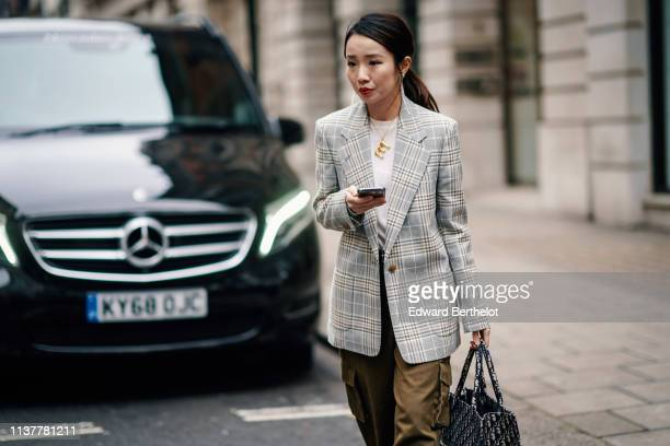 A guest wears earrings a white top a light grey Prince of Wales jacket khaki wideleg pants with sidepockets a Dior monogram tote bag during London...