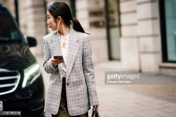 A guest wears earrings a white top a light grey Prince of Wales jacket khaki pants during London Fashion Week February 2019 on February 16 2019 in...