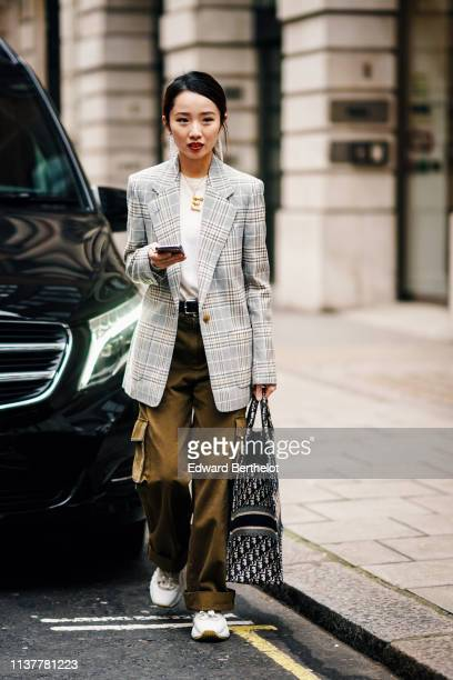 A guest wears earrings a white top a light grey Prince of Wales jacket khaki wideleg cuffed pants with sidepockets a Dior monogram tote bag white...