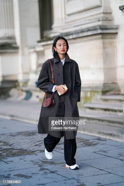 A guest wears earrings a white top with a lavaliere a burgundy embossed leather bag a dark grey checkered trench coat black widelegs pants white Nike...