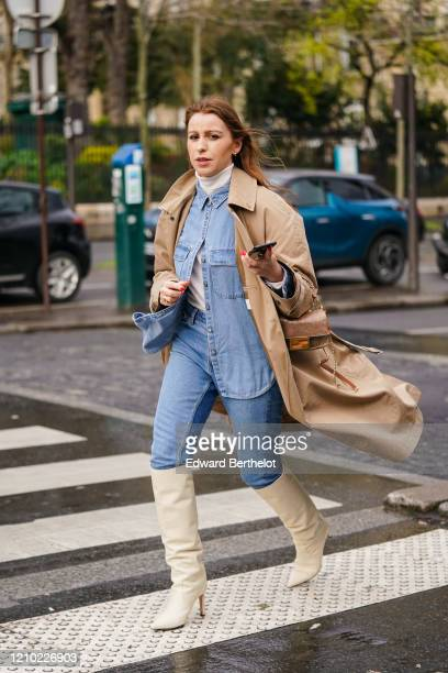 Guest wears earrings, a white turtleneck, a blue denim shirt, blue jeans, a sand-color trench coat, white pointy heeled knee-high boots, a Fendi bag,...
