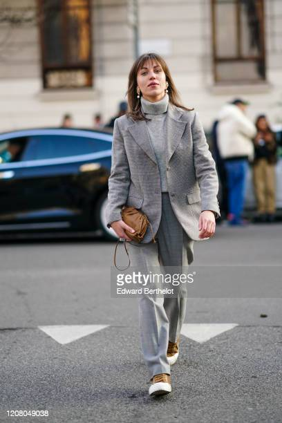 Guest wears earrings, a wool turtleneck pullover, a gray blazer jacket, a brown leather bag, flared large pants, outside Bottega Veneta, during Milan...