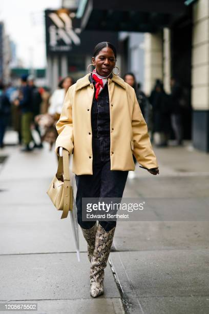 A guest wears earrings a yellow jacket a scarf a denim jumpsuit cowboy snake print boots during New York Fashion Week Fall Winter 2020 on February 11...