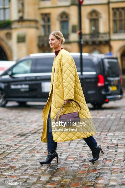 Guest wears earrings, a yellow quilted long coat, a purple leather bag, black leather pointy boots, blue jeans, during London Fashion Week Fall...