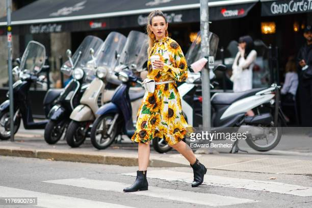 Guest wears earrings, a yellow sunflowers print dress with a frilly collar and a ruffled hem, a Dolce & Gabbana white belt bag, Dolce & Gabbana black...