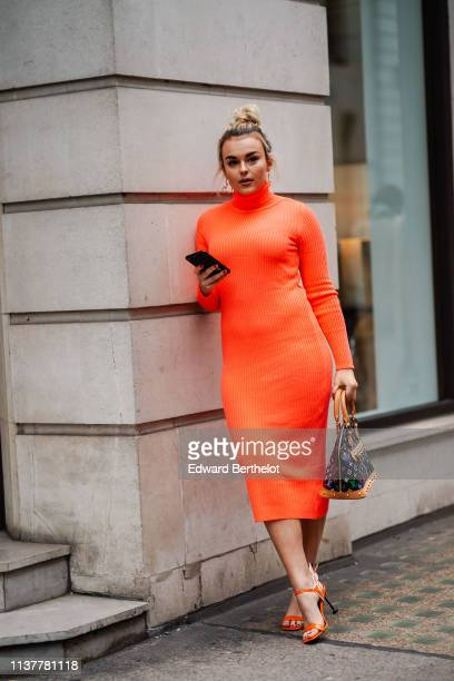 A guest wears earrings an orange turtleneck dress a Louis Vuitton handbag orange heeled sandals during London Fashion Week February 2019 on February...