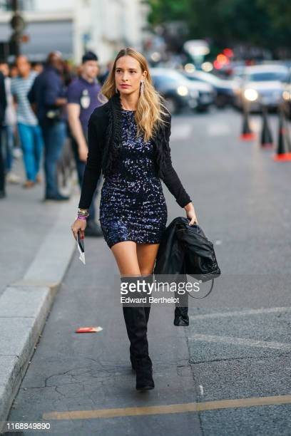 A guest wears earrings bracelets a black fringed jacket a glittering sequined navy blue mini dress a black quilted bag black suede kneehigh pointy...