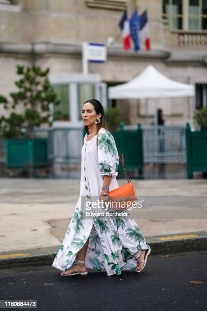 A guest wears earrings bracelets a puff sleeves white long ruffled dress with green coconut tree pattern an orange Loewe bag white gladiator flat...