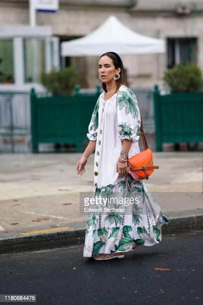Guest wears earrings, bracelets, a puff sleeves white long ruffled dress with green coconut tree pattern, an orange Loewe bag, white gladiator flat...