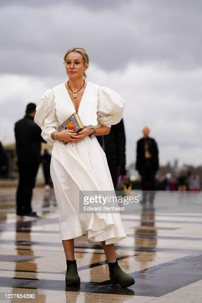 Guest wears earrings, bracelets, a watch, a Dior necklace, a V-neck white dress with a scalloped hem large collar and puff sleeves, an Alice in...