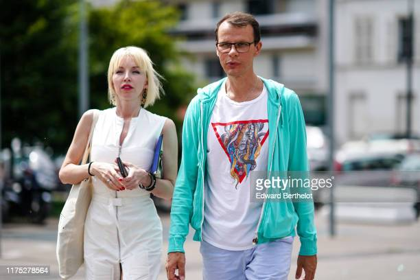 Guest wears earrings, bracelets, a white dress with a front zip, a beige tote bag ; A guest wears a white t-shirt with a picture print on the chest,...