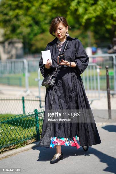 A guest wears earrings Chanel necklaces a black Chanel studded bag a black flowing trench coat a colorful skirt shiny golden and black Chanel...