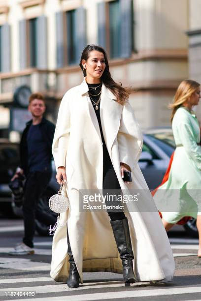 Guest wears earrings, necklaces, a black top, a white oversized full length coat, a crystal beads ball-shaped minaudiere with pompoms, black...