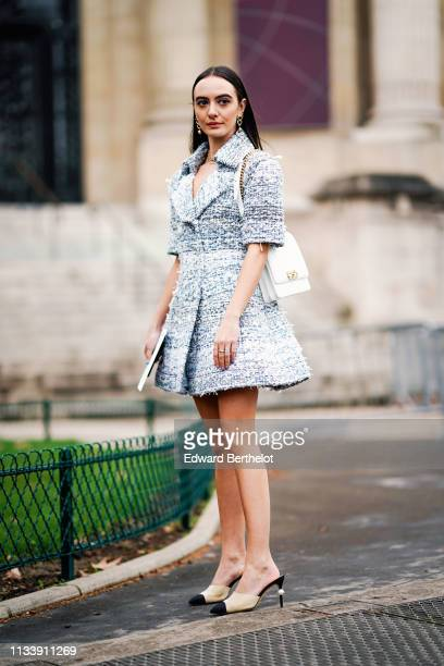Guest wears earrings, necklaces, a blue and white tweed dress with short sleeves, black and beige mules with a pearl at the heels, a white Chanel...