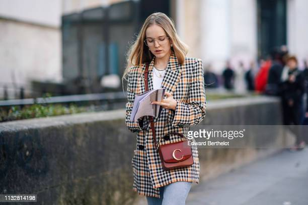 Guest wears earrings, necklaces, a brown Chloé bag, a black and camel checkered jacket, a white top, outside Dries Van Noten, during Paris Fashion...