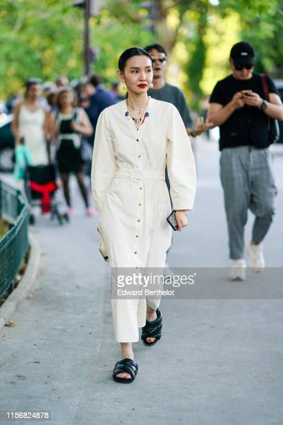 Guest wears earrings, necklaces, a cream-color V-neck long dress, black padded flat sandals, outside AMI, during Paris Fashion Week - Menswear...