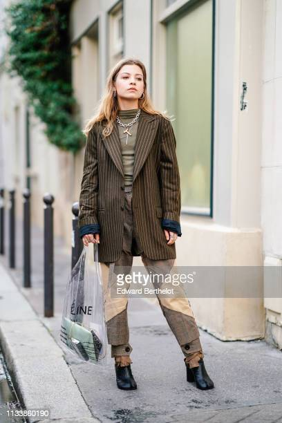 A guest wears earrings necklaces a khaki turtleneck a brown oversize jacket with thin stripes brown pants with camel inserts separated end black...